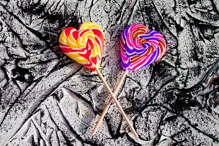 Heart shaped lollipops on  black white abstract background. Top view. Stok Fotoğraf