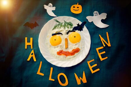 Breakfast omelette for Halloween. Paper text halloween and pumpkin, bat and cast from paper Stok Fotoğraf