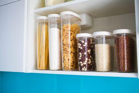 Despensa de cocina surtida con alimentos: pasta, trigo sarraceno, arroz y azúcar, vista lateral. La organización y almacenamiento en cocina de un estuche con grano en recipientes de plástico. Foto de archivo