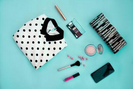 Women is dress print polka dots, bag, cosmetics, lipstick, eye shadow, powder, blush , mascara and smartphone on a blue background. Stok Fotoğraf