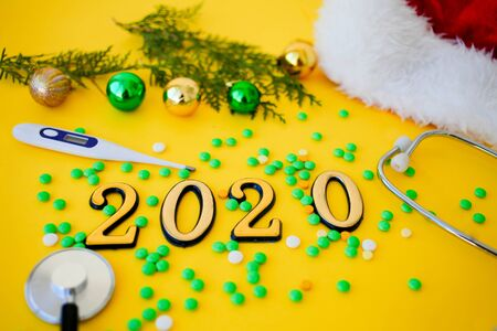 Stethoscope with 2020 number thermometer, pills and christmas balls  on yellow background. Happy New Year for health care and medical bannercalendar cover. Side view