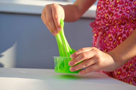 Hand holding homemade toy called Slime, kids having fun and being creative by science experiment. Close up of a little girl is hand playing a green slime
