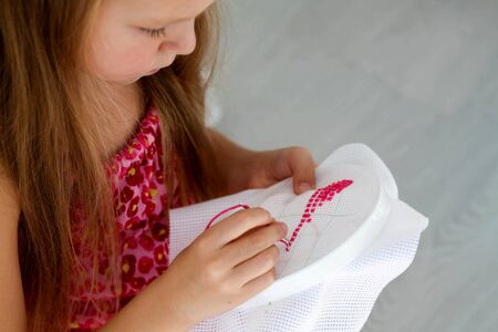 Little girl learning to embroider a cross-stitch.