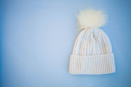 White knitted hat on a blue background. Copy space Stock fotó