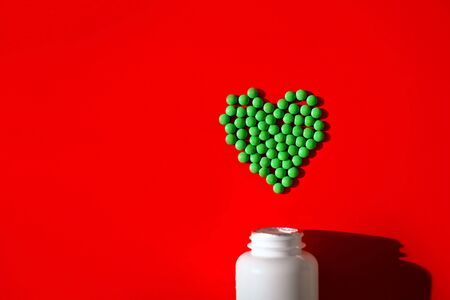 The heart made of green tablets and pills on red background
