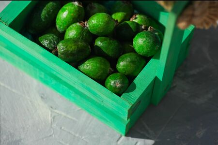 Green feijoa in a wooden box on a gray background Stock fotó