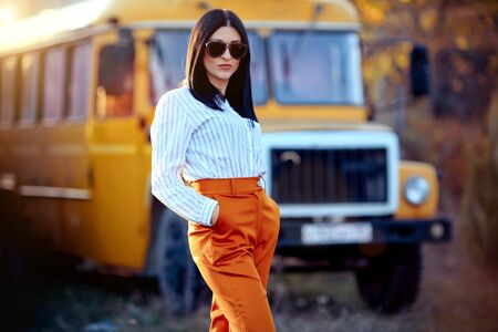 A trendy stylish business woman in the sunglasses against the background of an orange bus. Autumn style of clothes
