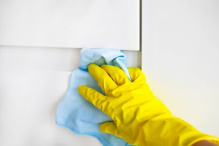 A female hand in yellow rubber gloves wipes a modern white kitchen with a microfiber cloth. Foto de archivo - 134613531