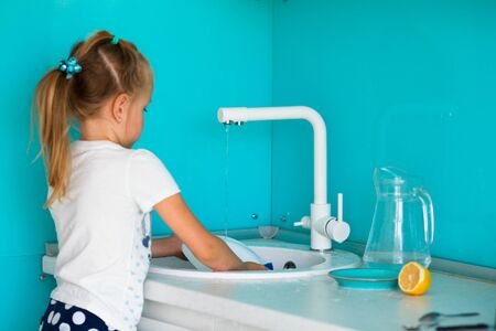 Little girl washes dishes at the kitchen sink in the kitchen