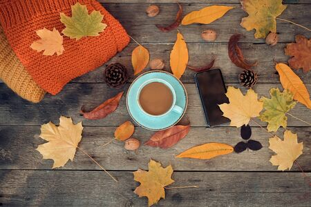 Cup of coffee, autumn leaves and a smartphone on a wooden background. Top view . Stock fotó