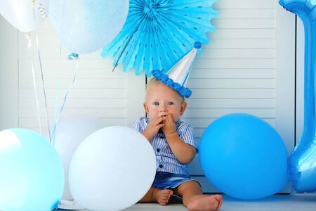 Little boy celebrates his 1 year birthday. Baby sits in a cap among blue balloon Stock fotó