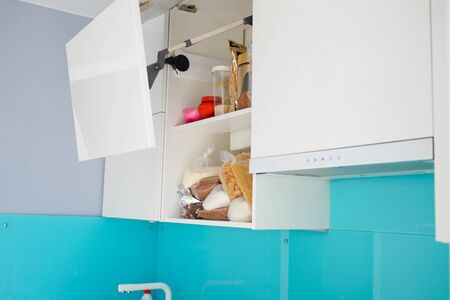 Unorganized storage of cereals in the kitchen cabinet. Modern white kitchen without handles. Stock fotó