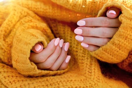 Beautiful female oval shaped pink manicure in an orange sweater. Pink caramel nails, gel polish. Stock fotó