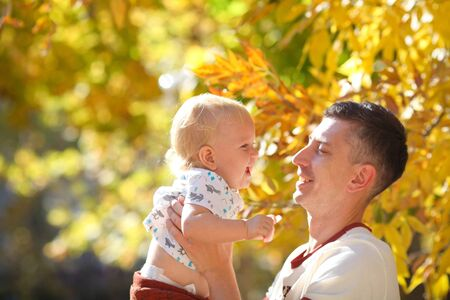 Happy father holds in his hands a charming baby in the autumn park. Father and son spend a day together. Stock fotó
