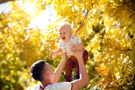 Happy father throws his adorable baby up in autumn park. Father and son spend a day together.
