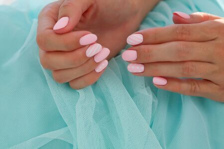 Summer gentle manicure in pink on a blue background. Caramel nails, copy space