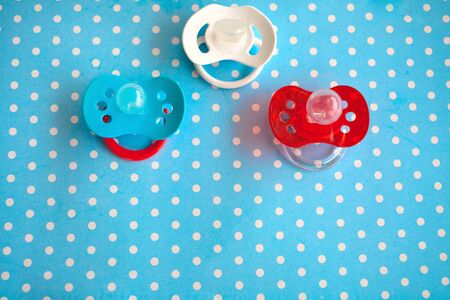 Three of babies silicone dummies pacifier on a blue background. Copy space. Фото со стока