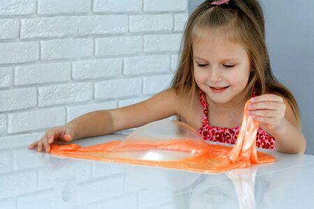 Girl playing hand made toy called slime. Children play with big orange slime. Kid squeeze and stretching slime. 写真素材