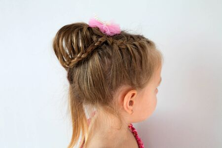 Assembled up hairdo of a little girl from pigtails on a white background. Home hairstyle, hands mom. Side view