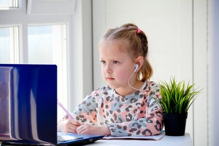 Girl schoolgirl in headphones looks at a laptop and writes in a notebook. Distance learning, study at home, online.