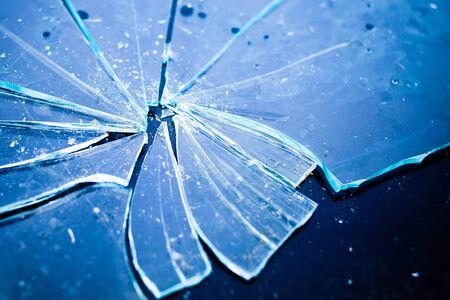 Detail of shattered glass on black background. Texture of broken glass in blue light