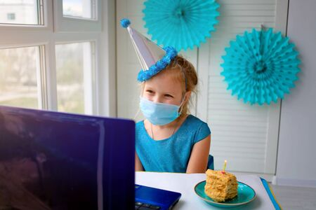 A happy little girl, wearing a medical mask in front of her laptop celebrates her birthday via the internet in quarantine time, self-isolation, online birthday. Congratulations to the animator Banque d'images