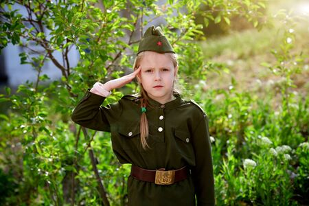 Portrait of a girl in uniform put a hand to her head on a green background. Victory Day, May 9 holiday. Фото со стока