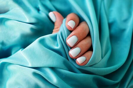 Female hands with a beautiful manicure on a blue background. Summer trend, blue gradient on the nails with gel polish, shellac. Short nails