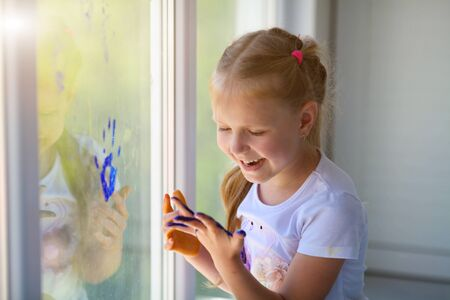 Portrait of a happy little girl draw palms on the window. Painted children's hands leave a mark on the glass. Quarantine. Stay home. Flash mob society community on self-isolation quarantine pandemic . Standard-Bild