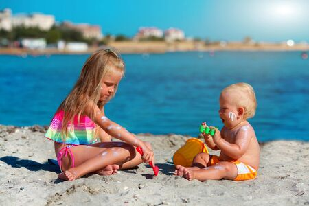 Children play on the beach. Summer water fun for the family. Boy and girl with toy buckets and a shovel on the seashore. Sunscreen applied to children is skin