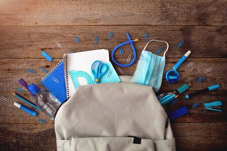 Backpack with blue school supplies and medical mask on wooden background. View from above. Back to school after quarantine concept.