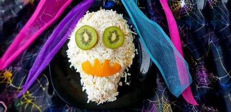 Skull-shaped halloween holiday salad decorated with kiwi and orange trigger