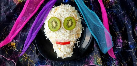 Halloween holiday salad decorated in the shape of a funny skull, decorated with kiwi  Stock Photo