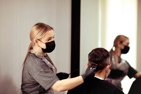 A hairdresser with security measures for Covid-19, cuts a man in a medicine mask, social distance, cutting hair with a medical mask and rubber gloves. Stock Photo
