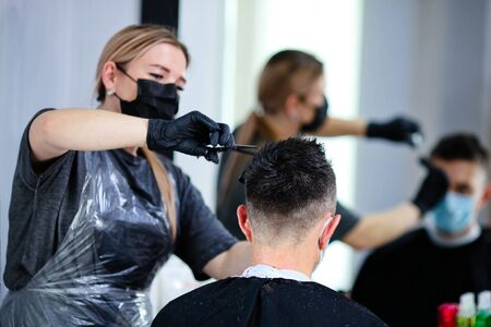 Close up hairdresser with security measures for Covid-19, cuts a man  social distance, cutting hair with a medical mask, face shield and rubber gloves. Stock Photo