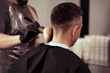 A hairdresser with security measures for Covid-19, holds scissors in his hands and cuts a man, social distance, cutting hair with rubber gloves