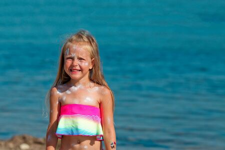 A beautiful little girl smiles in a swimsuit standing by the sea with sunscreen smeared on her face. Copy space Stock Photo