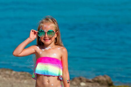 Beautiful little girl in a swimsuit and sunglasses stands by the sea with sunscreen smeared on her body. Copy space Stock Photo