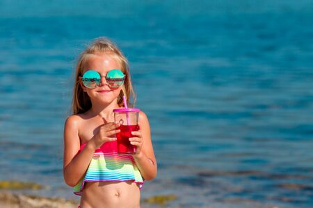Beautiful little girl in a swimsuit and sunglasses stands by the sea and holds fruit drinks from a glass in her hands. Copy space