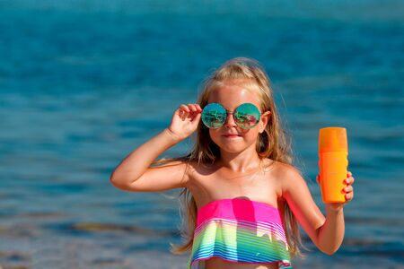 Beautiful little girl in a swimsuit and sunglasses stands by the sea and holds a sunscreen in her hands. Copy space