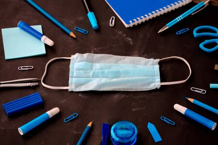 School and office supplies on a black school board background: felt-tip pens, pens, blue color pencils. Concept: return to school in a new reality. Flatlay, top view.