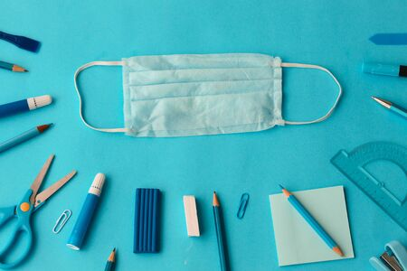 School and office supplies on a blue background: felt-tip pens, pens, colored pencils in blue. Concept: return to school in a new reality. Flatlay, top view.
