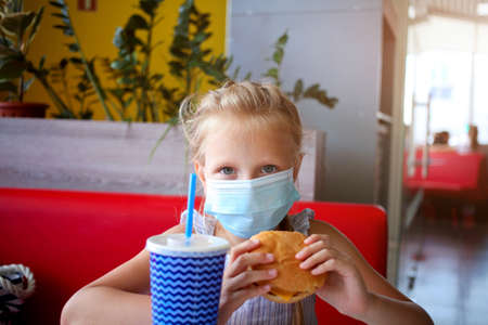 A little girl sits in a cafe in a medical mask and holds a burger and soda in her hands. Opening a cafe. Work cafe with security measures for Covid-19. Work during covid-19 or coronavirus