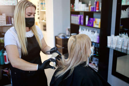 Hairdressing salon opened. Hairdresser with security measures for Covid-19, a woman in a medical mask, social distance, cutting hair with a medical mask and rubber gloves in a beauty salon