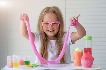 A little girl in pink glasses pulls the mucus up. Children is hands playing slime toy. Make mucus. Copyspace.