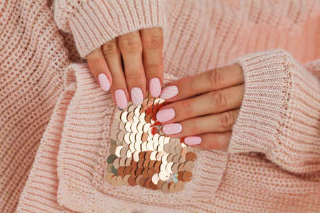 Female hands with beautiful oval-shaped nails, matte pink manicure close-up on a pink knitted sweater background. Shellac. Copy space Stock Photo