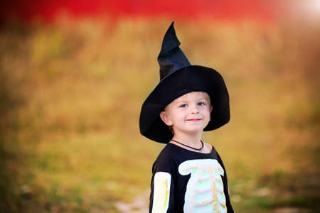 Portrait of a little boy wearing a skeleton costume and a black hat. Halloween holiday. Baner. Copy space. 스톡 콘텐츠