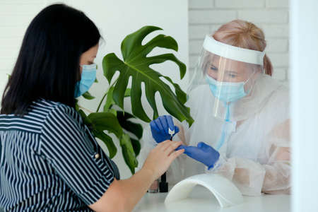 Manicurist in are wearing PPE paints nails in a beauty salon. ... The existence of small businesses in isolation from COVID-19. A woman in a medical mask and rubber gloves makes a manicure Reklamní fotografie