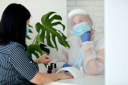 Manicurist in are wearing PPE paints nails in a beauty salon. The existence of small businesses in isolation from COVID-19. Woman in medical mask and protective suit dreams of the end of quarantine