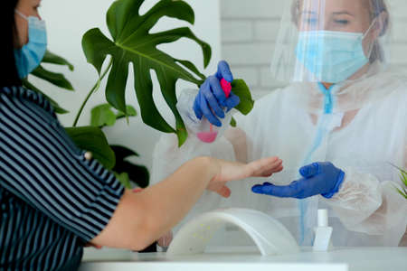 A manicurist in a protective mask and clothes in a beauty salon treats his hands with an antispecialist. Professional procedure. Existence of small businesses in isolation from COVID-19. A woman in a medical mask and rubber gloves makes a manicure